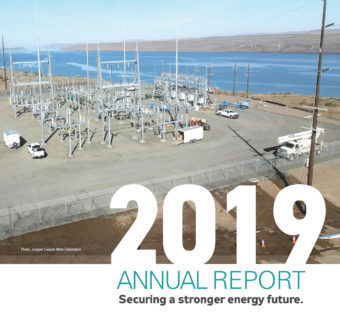 2019 Annual Report, Securing a stronger energy future. Photo of construction with a lake behind.