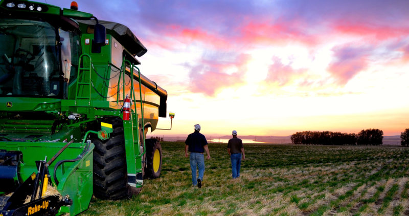 Two men near tractor with sunset in the distance