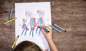 A child drawing a family with crayons.