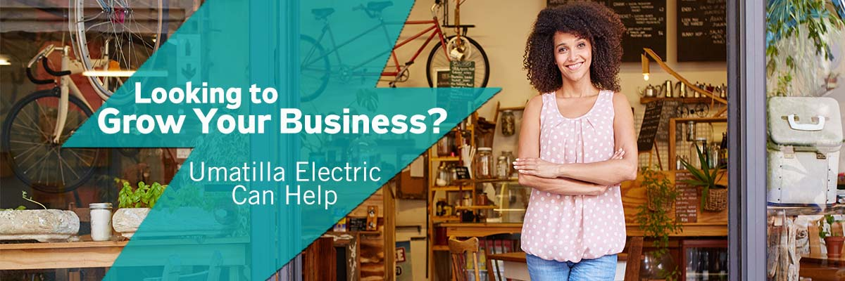 Woman standing in front of a business storefront. Looking to grow your business? Umatilla Electric can help.