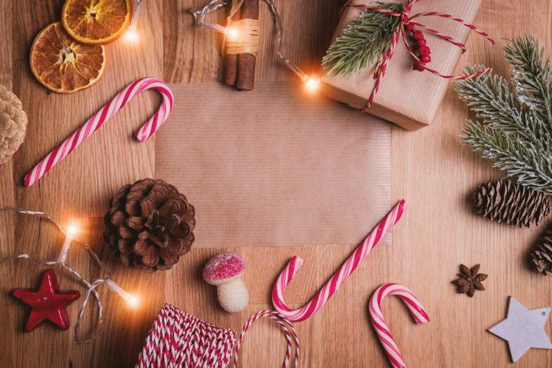 Candy canes, acorns, string lights, a present, sitting on a table.