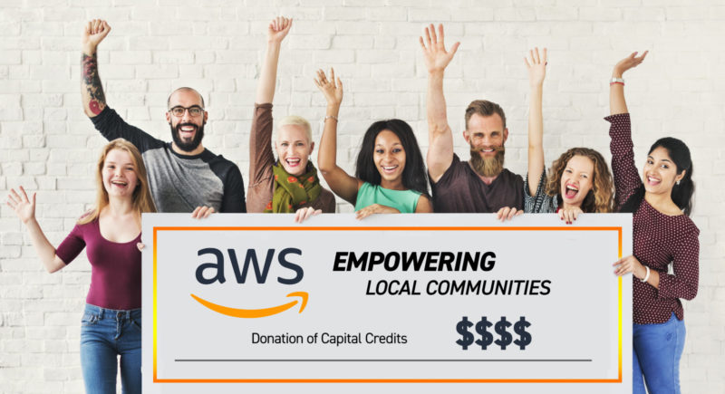 Several men and women with their hands raised in the air, holding a big check: AWS, Empowering local communities. Donation of capital credits.